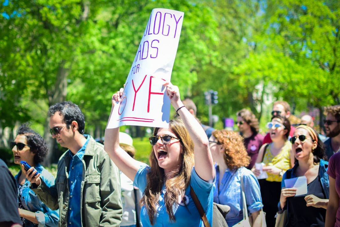 A Northwestern graduate worker at a protest holds up a sign for 6th year funding