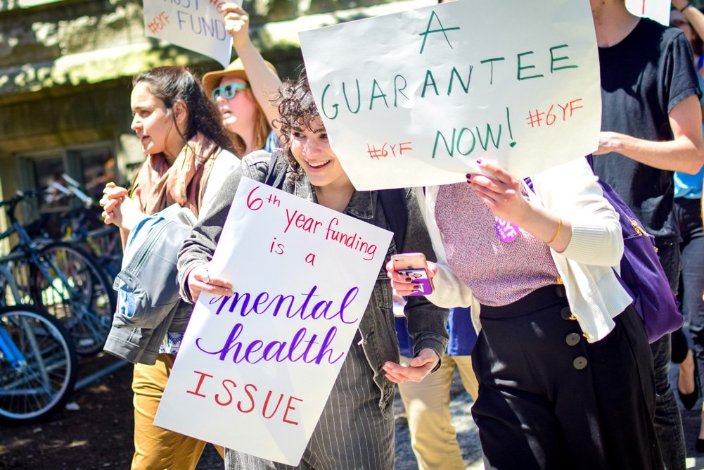 """Two graduate workers hold up signs at a protest. One reads """"6th year funding is a mental health issue."""" The other reads """"A guarantee now!"""""""